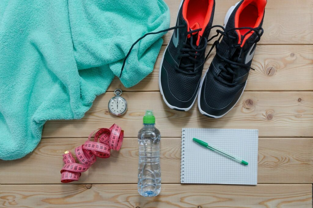 Personal training photo with water bottle, turquoise towel, notebook, stopwatch, and black sneakers.