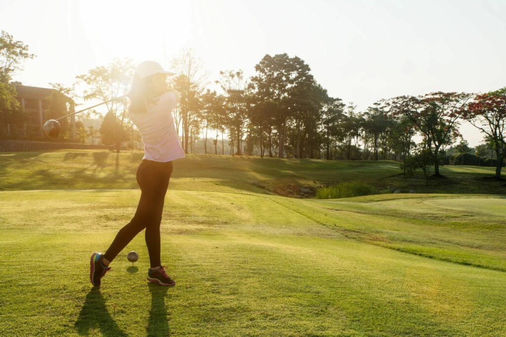 Woman in pink shirt and black leggings taking a swing at the golf ball on the course.