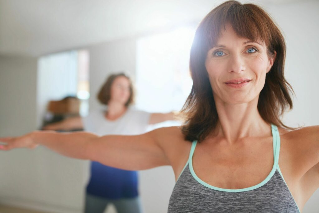 Blue-eyed woman with gray and turquoise tank top on training in a fitness class.