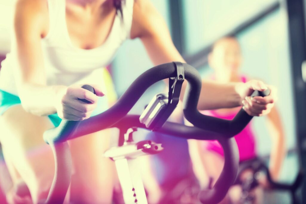 Spinning class with woman dressed in turquoise and white on the front bike.