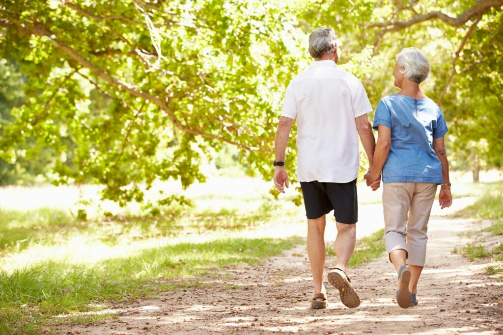 Functionally aging man and woman taking a walk while holding hands on a dirt path with trees around.