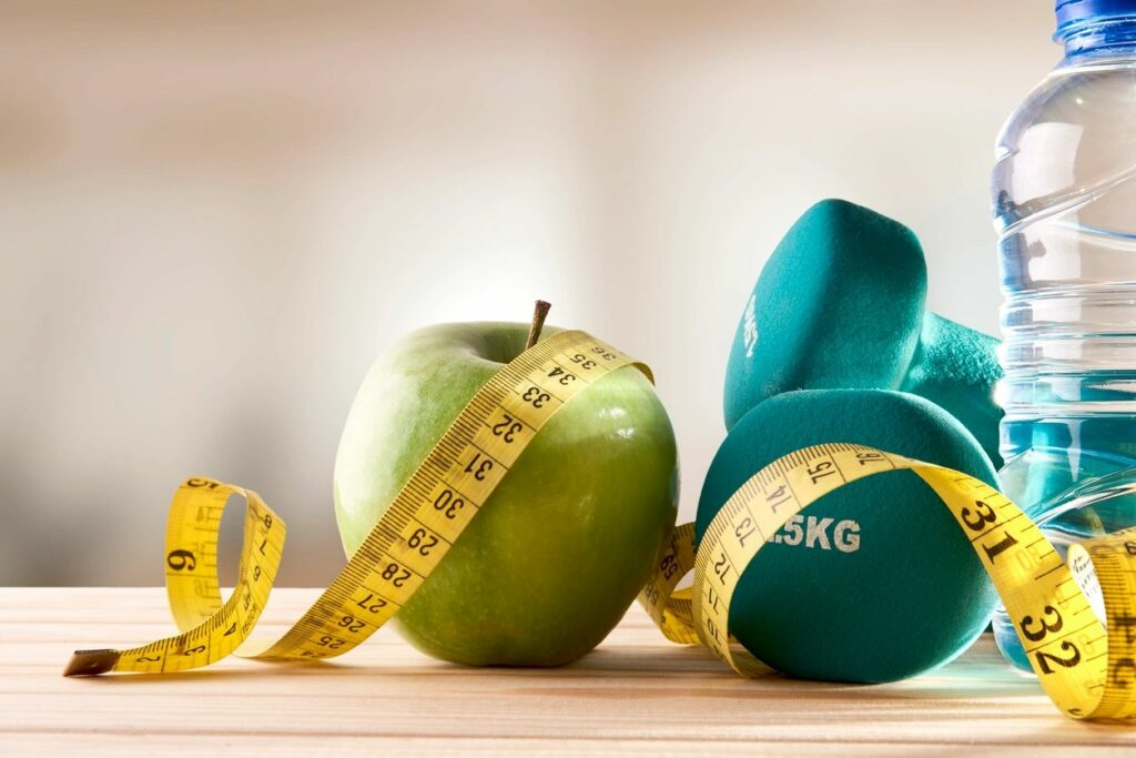 Healthy photo with green apple, turquoise weights, bottle of water, and yellow measuring tape.