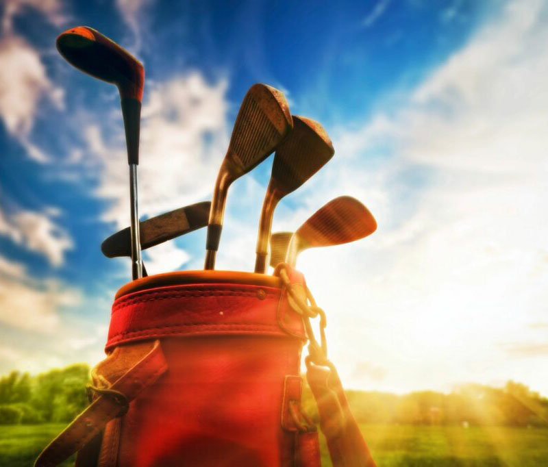 Red golf bag with golf clubs with blue skies and greens in the background